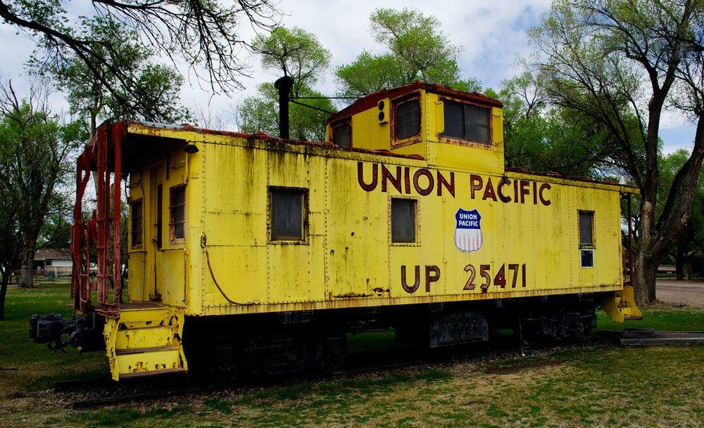 yellow train on rail tracks